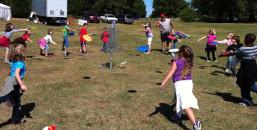 School children learning disc golf skills at the EDGE Pavilion at the USDGC.