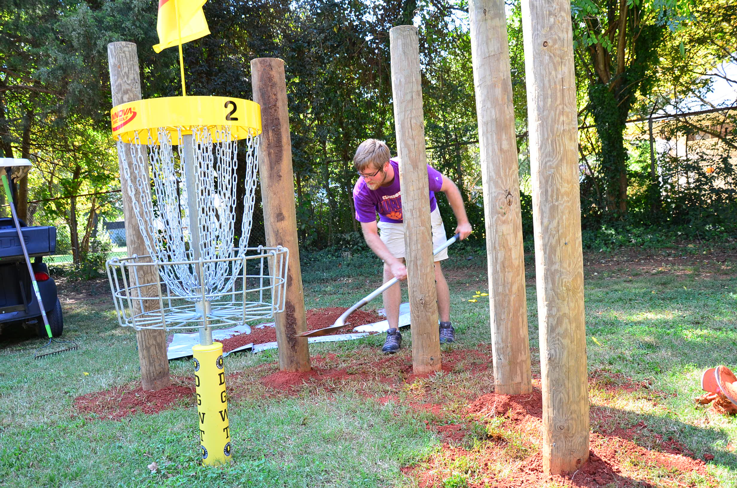 USDGC Staffer smoothes out the dirt surounding the newly planted pillars